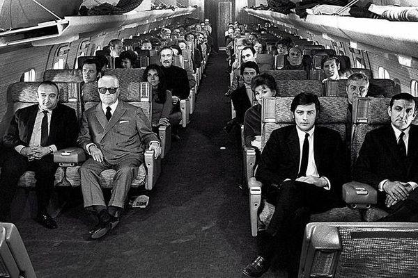 Jean Gabin, Lino Ventura, Alain Delon et d'autres acteurs assis dans un avion.