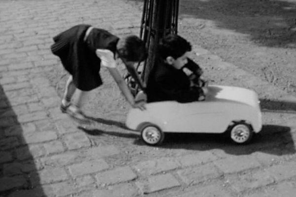 Un petit garçon d'environ 4 ans, François, et sa sœur Laurence jouent aux petites voitures en 1960.