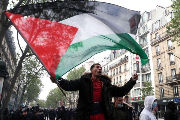 Un homme brandissant un drapeau palestinien lors d'une manifestation le 15 mai 2021 à Paris. Geoffroy Van Der Hasselt/AFP