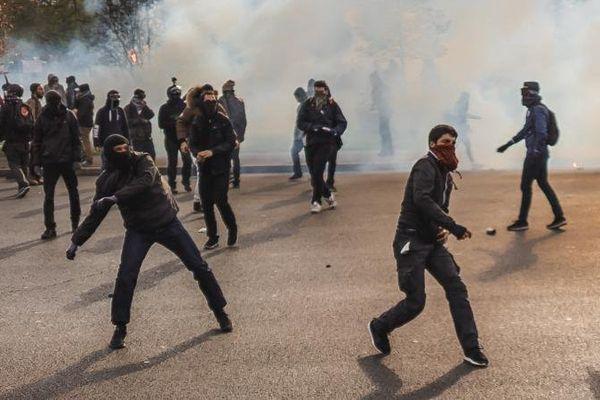 Des manifestants masqués jettent des projectiles en direction de la police, place de la Nation à Paris, après la manifestation contre la loi Travail, le 28 avril 2016.