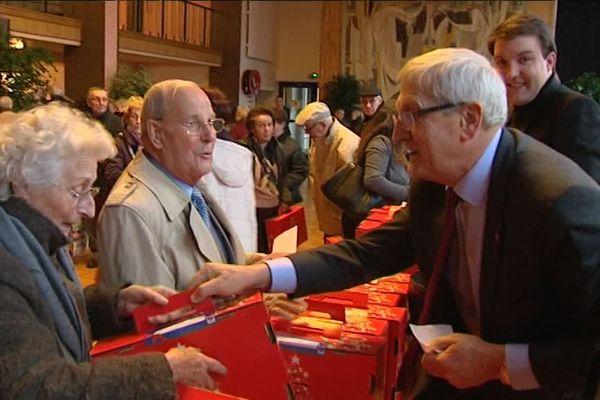Le maire de Limoges Emile-Roger Lombertie et ses adjoints remettent les colis de Noël aux ainés de la ville.