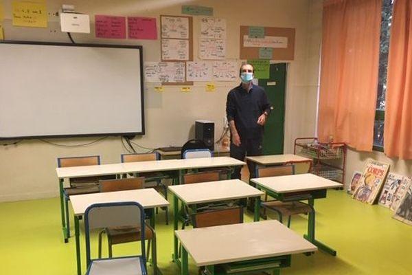 Un enseignant prépare sa classe avant d'accueillir ses élèves dans quelques jours, le 11 mai à Melun en Seine-et-Marne.