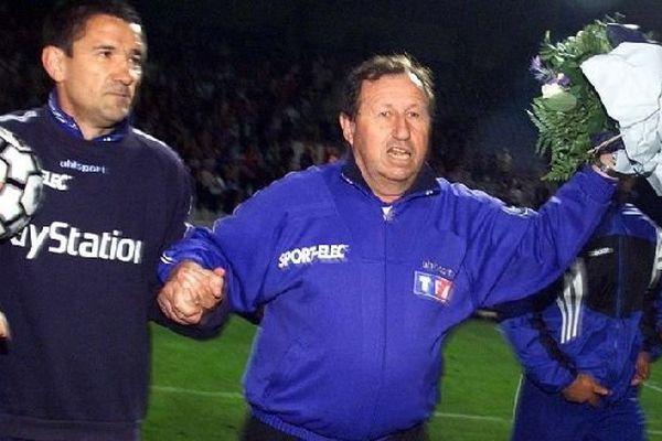 L'entraîneur de l'AJ Auxerre, Guy Roux (C), accompagné de son entraîneur-adjoint Dominique Cuperly, salue le public lors d'un tour d'honneur, le 04 mai 2000 au stade de l'Abbé Deschamps à Auxerre, à l'issue de la rencontre Auxerre/Rennes (4-0), comptant pour la 33e journée du championnat de France de Football de D1.