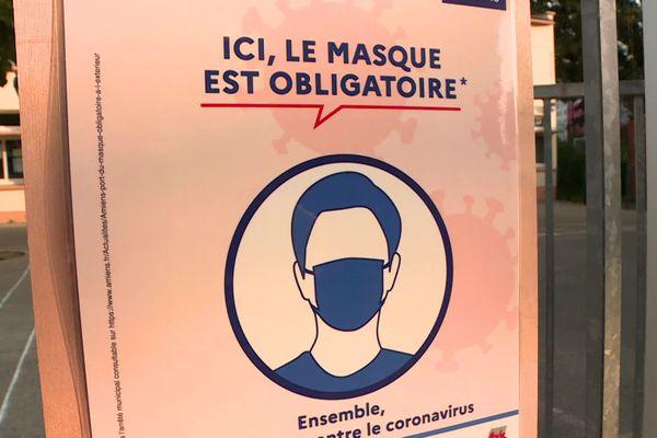 Panneau imposant le port du masque devant une école
