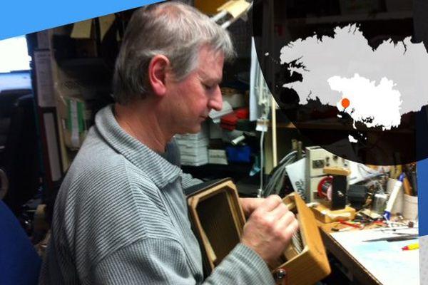 Dans son atelier, Bernard, concentré travaille sur un accordéon