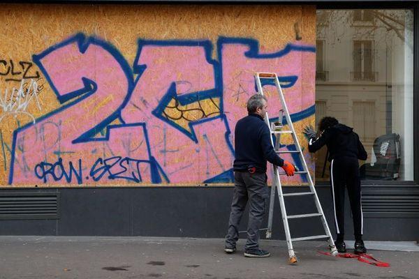 Des commerçants installent des panneaux pour protéger leur établissement avant une manifestation contre la réforme des retraites, le 17 décembre 2019.