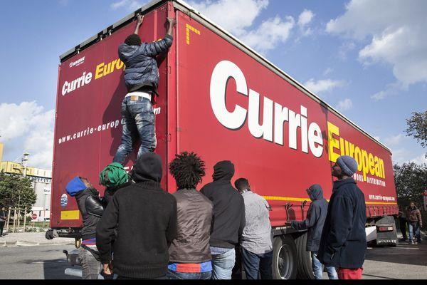 Des migrants profitent d'un pause dans une station service de Calais pour tenter de pénétrer dans ce camion et essayer de rejoindre l'Angleterre.