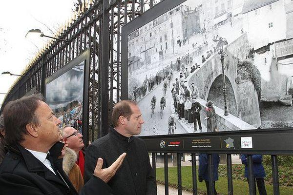 Jean-Pierre Bel, Président du Sénat accompagné de Christian Prudhomme, Président du Tour de France, sous une photo de l'exposition pour les 100 ans du Tour de France.