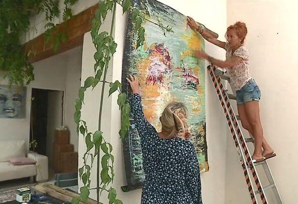 Jacqueline accroche l'une de ses oeuvres avec l'aide de Michelle