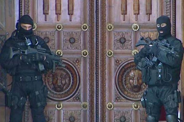 Des gardes armés jusqu'aux dents, devant la salle d'assises.