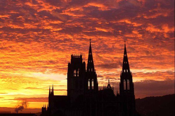 La cathédrale de Rouen dessine sa dentelle de pierre sur la palette du soleil levant pour toile de fond.