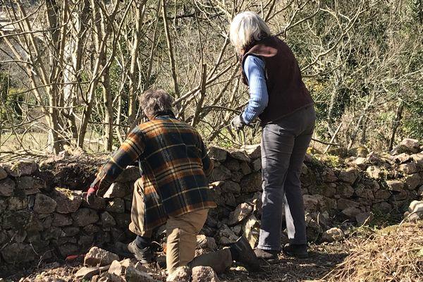Deux bénévoles de l'association du Parc Joly à Semur-en-Auxois(21), remontent un mur de pierres sèches.