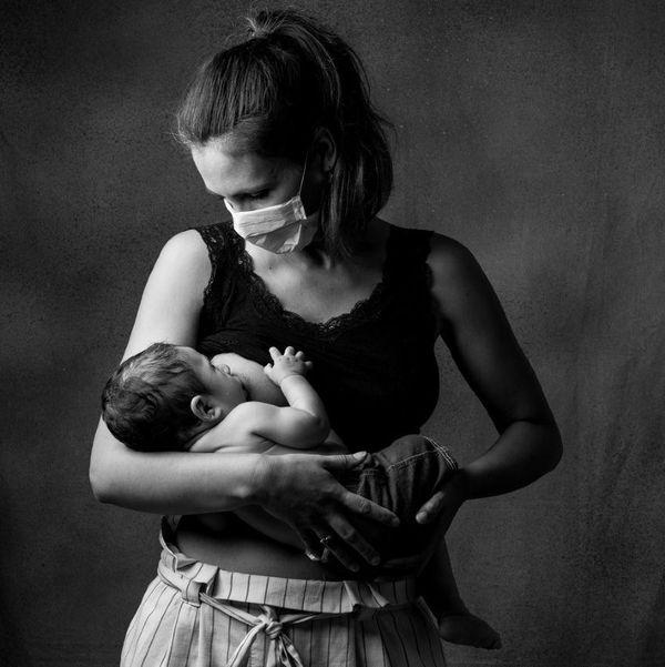 Mère allaitant son nouveau-né en 2020. Son sein droit est dénudé mais le bas de son visage est masqué. Elle et son enfant se regardent.