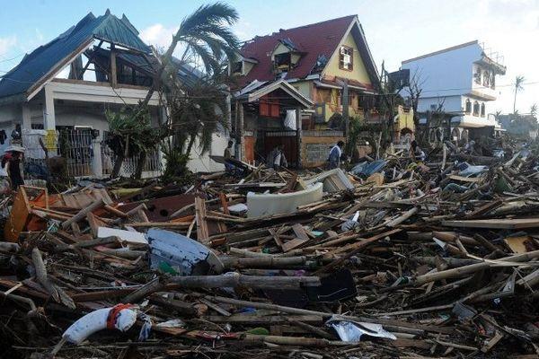 Des habitants marchent au milieu des débris et des maisons détruites à Palo, à l'est de l'île de Leyte, le 10/11/2013, 3 jours après le passage du super typhon Haiyan.