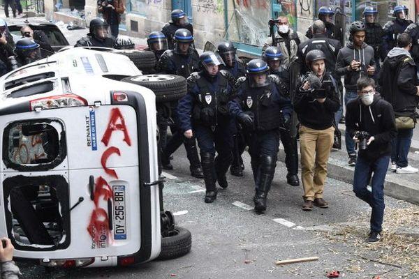 Les CRS et des observateurs à côté d'un véhicule vandalisé par les manifestants.