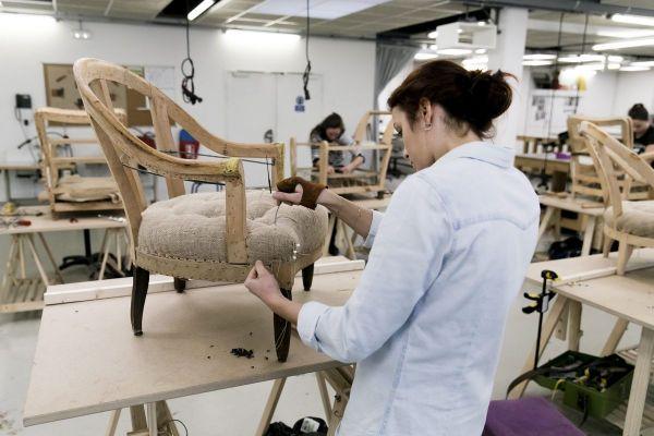 Une jeune apprentie en train de travailler dans un atelier de fabrication de fauteuils.