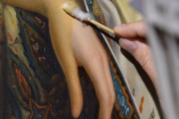 Grâce à une solution et du coton, Aurélie Briot, restauratrice d'oeuvres d'art, redonne une seconde jeunesse à ce tableau datant du XIXe siècle.