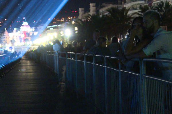 Un couple assiste à la projection des 86 faisceaux lumineux sur les lieux de l'attentat.