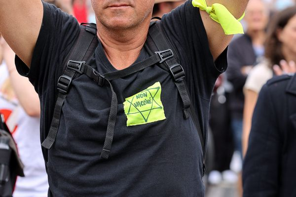 """Un homme porte une étoile jaune sur laquelle est inscrite """"non vacciné"""" lors d'une manifestation contre l'extension du pass sanitaire à Paris, le 17 juillet 2021."""