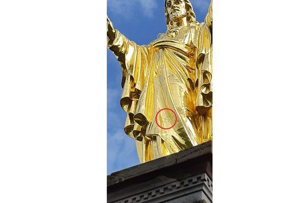 La croix gammée nazie a été tracée sur l'or fin recouvrant la statue, à l'aide d'une pointe.