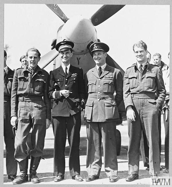 """René Mouchotte, en mai 1943, aux côtés de Jack Charles, leader du 611 Squadron (à gauche), et de deux légendes de la Royal Air Force Force, héros de la Bataille d'Angleterre (à droite) : le Sud-Africain Adolph """"Sailor"""" Malan, commandant de Biggin Hill, et le Néo-Zélandais Al Deere, wing commander."""