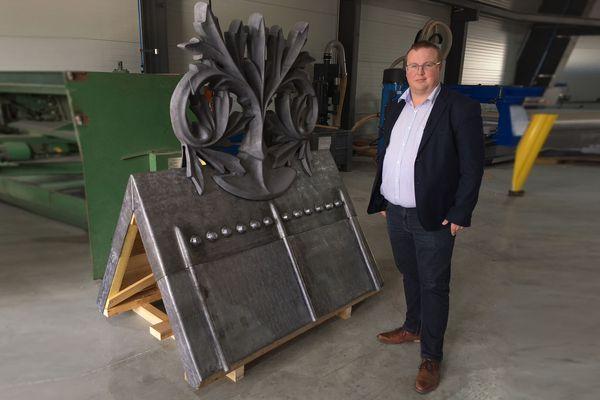 Julien le Bras près de la maquette réalisée par les couvreurs de l'entreprise Le Bras Frères en septembre 2019. Elle présente un moulage neuf basé sur une crête de toiture originale restaurée en 1856 par Viollet-le-Duc.