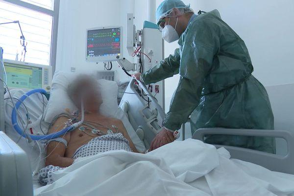 Le docteur Pierre-Marie Bertrand au chevet d'un patient atteint de la Covid-19 et placé sous assistance respiratoire.