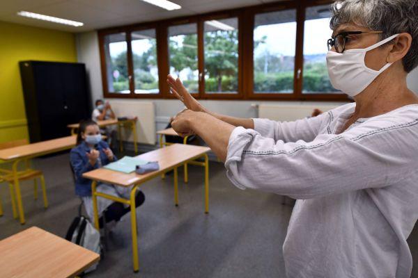 Une infirmière scolaire explique, dans une salle de classe, à des élèves de 6ème comment bien se laver les mains.