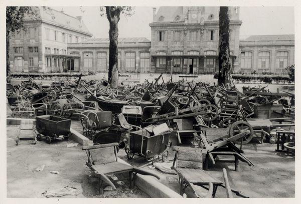 Brouettes et landaus abandonnés devant la gare de Charleville après le départ d'un train. Photo allemande.