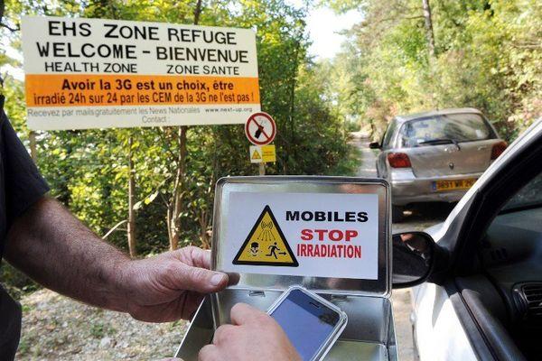 """Une personne dépose son téléphone portable à l'entrée du premier refuge anti-ondes de France, près de Crest, en 2009. Perché sur une colline, sans habitation ou antennes-relais aux alentours, l'abri est conçu pour les victimes de l'électro-hyper sensibilité (EHS). A l'entrée de cette """"zone blanche"""", dont la localisation exacte est tenue secrète, les téléphones portables, même éteints, sont proscrits et rangés dans une boîte métallique isolante."""