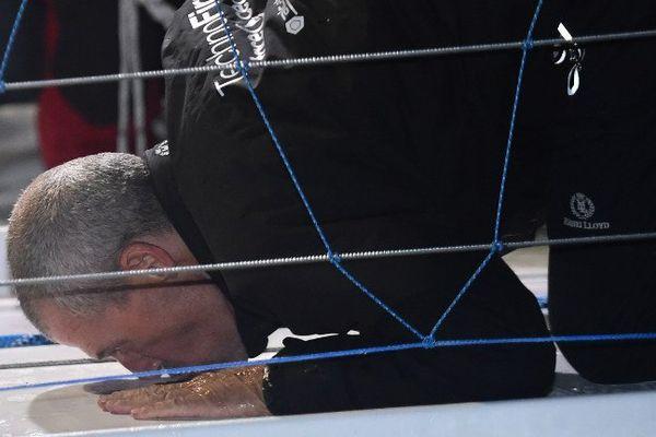 Sébastien Destremau embrasse le pont de son bateau après avoir franchi la ligne d'arrivée du Vendée Globe, le 11 mars 2017.