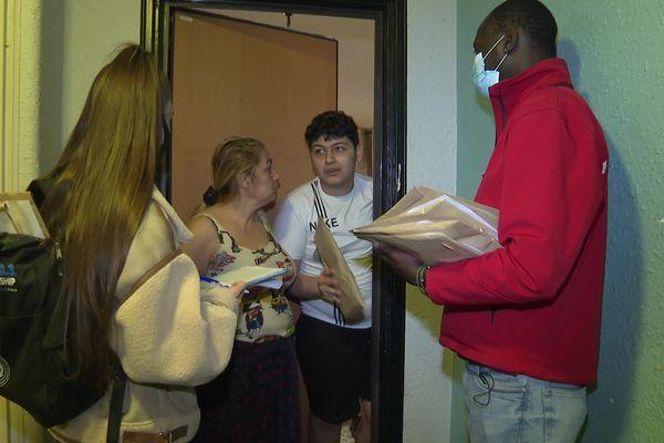 Deux bénévoles de l'association Adam font du porte-à-porte pour donner des masques et du gel hydroalcoolique dans le quartier des trois Moulins à Nice (Alpes-Maritimes).