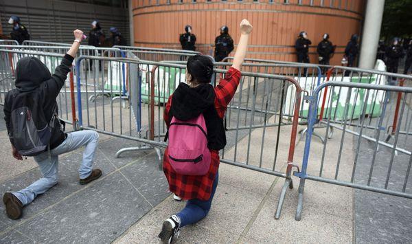 """Arrivés devant le palais de justice des manifestants ont mis un genou en terre en signe de protestation contre les """"violences policières""""."""