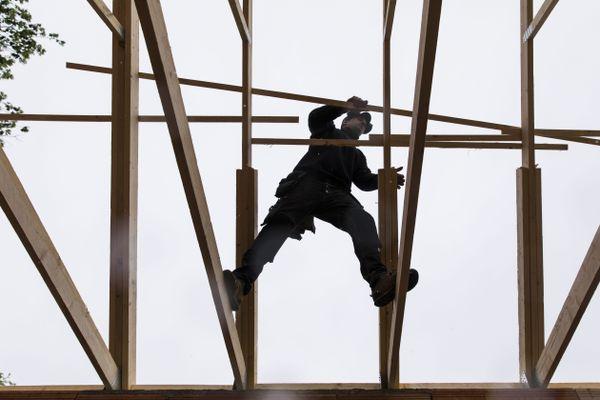 Un ouvrier en équilibre entre les deux poutres d'un échafaudage - Photo d'illustration