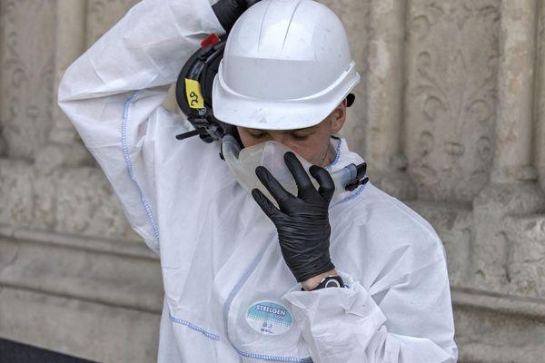 Un employé enfile sa tenue de protection avant de pénétrer dans le chantier de la cathédrale Notre-Dame de Paris.