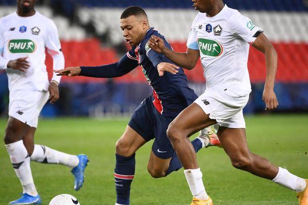 L'attaquant du Paris-Saint-Germain Kylian Mbappé aux prises avec un joueur du LOSC Lille. Photo AFP