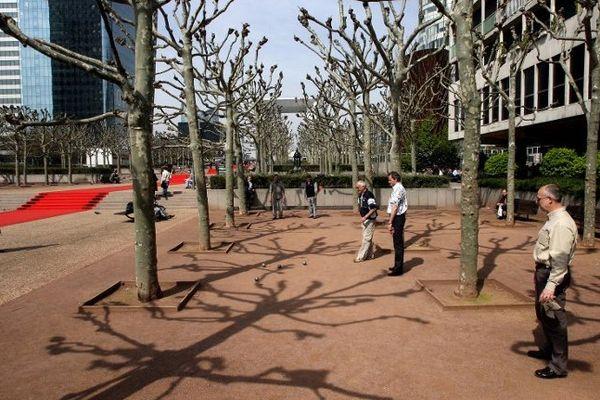Des employés de bureau parisiens jouent à la pétanque dans le quartier de la Défense.