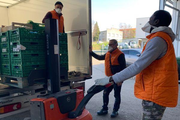 Equipés de masques, les bénévoles de la banque alimentaire réceptionnent de nombreux lots de denrées alimentaires dans leur entrepôt de Limoges