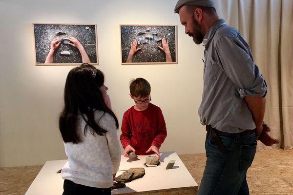 L'artiste accompagne des enfants à la découverte d'un puzzle de pierres, thème de son exposition