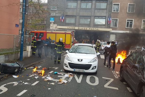Les pompiers éteignent les poubelles devant le lycée Blaise Pascal à Clermont-Ferrand.