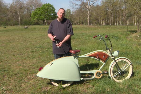 """Jérémy Delignières et son vélo """"Deudeuche"""", la toute dernière de ses créations home-made à Cerdon (Loiret). Il tient dans ses mains le réservoir 2CV sur lequel est arrimée la clef pour réparer les roues. Si besoin"""
