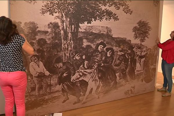 """Accrochage d'une reproduction du tableau polémique et anticlérical de Gustave Courbet """"Le Retour de la conférence""""."""