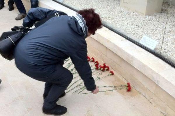 Dépôt d'oeillets rouge pour protester contre la venue de Marine Le Pen au Mémorial pour la Paix à Caen.