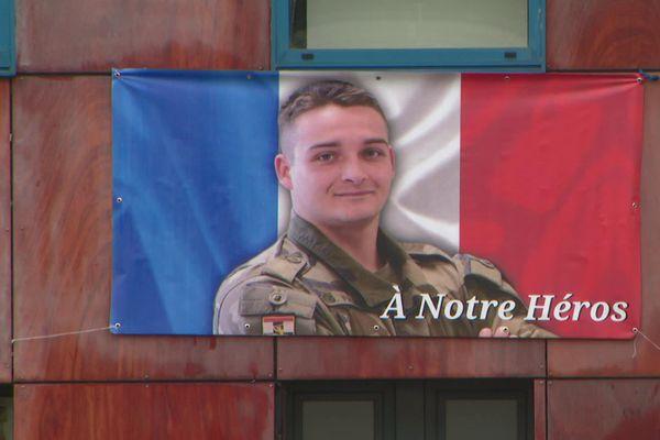 """""""À notre héros"""". Ce drapeau orne les façades de nombreux commerces et bâtiments de la commune."""