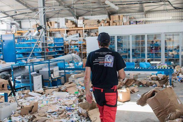 Des pompiers de l'urgence internationale dans un entrepôt pharmaceutique dévasté à Grand Case sur l'île de Saint-Martin le 14 septembre, à la recherche de médicaments