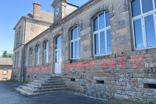 Des inscriptions sur la façade de l'école de Gentioux-Pigerolles en Creuse où a été arrêtée une femme.