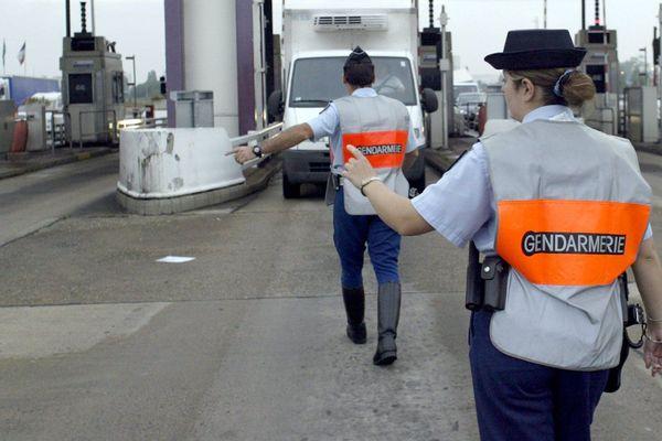 Photo d'illustration: Deux gendarmes arrêtent un camion au péage de Villefranche-sur-Saône.  - 07/07/04