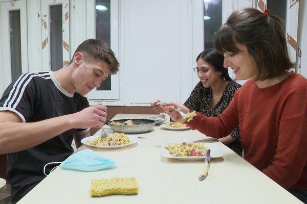 Valentin et Camille partagent avec Haïfa le repas qu'elle leur a préparé.