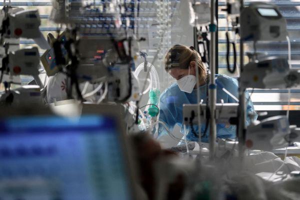 Une professionnelle de santé surveillant un patient en soins intensifs dans une unité Covid-19 en Suisse.