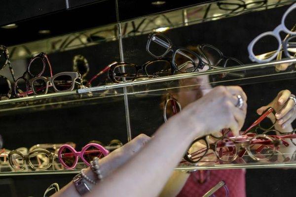 Une vendeuse place des paires de lunettes en vitrine chez un opticien de Lyon, le 9 septembre 2013.